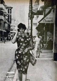 Dama Dominicana , camina escuchando su radio portatil , por la Calle El Conde de la Ciudad de Santo Domingo, Republica Dominicana. 1963 Fuente de la Imagen : Lorenzo Paulino Para Imágenes de Nuestra Historia , R.D