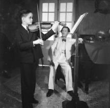"""CARLOS ALBERTO PIANTINI Interpreta el Violin en compañia de su profesor el Maestro Willy Kleinberg . En ese momento Piantini tenia la edad de 14 años 1941. Ciudad Trujillo , Republica Dominicana Fuente AGN -Conrado Carlos Piantini nació el 9 de mayo en el 1927, y muere el 26 de marzo del 2010 en la ciudad de Miami. Laureado músico y director de Orquesta Sinfónica en República Dominicana. La historia del internacionalmente aclamado director de orquesta Carlos Piantini comienza a la edad de diez años, cuando hizo su debut profesional como violinista. Desde entonces su pasión por la música le permitio disfrutar de una carrera exitosa. Antes de convertirse en director de orquesta, se desempeñó como violinista, durante quince años, en la Filarmónica de New York, bajo la dirección de Leonard Bernstein. Su decisión de convertirse en director lo llevó a Viena, donde estudió con el doctor Hans Swarowsky. El Maestro Piantini fue Director Titular Laureado de la Orquesta Sinfónica Nacional de República Dominicana, y también ostentó el cargo de profesor de estudios orquestales en la Universidad Internacional de la Florida. En el pasado ocupó importantes posiciones como la Dirección del Teatro Nacional de Santo Domingo, la conducción de la Orquesta Sinfónica Nacional y de la Orquesta Filarmónica de Maracaibo, Venezuela. Destacadas figuras internacionales han dado testimonios favorables sobre la carrera del Maestro Piantini. """"El señor Piantini es un director con autoridad, tiene ideas musicales y conoce profundamente su trabajo"""" (Zubin Mehta). La crítica del periódico francés """"Le Fígaro"""" agregó lo siguiente: """"Un director destacado posee un profundo sentido de sus intenciones. Carlos Piantini sabe comunicar su pasión y su musicalidad con sus interpretaciones"""". Raymond Erickson de """"The New York Times"""" comentó lo siguiente sobre el Réquiem de Verdi: """"Anoche Piantini cambió su violín por la batuta y condujo la Filarmónica extremadamente bien. Sus tempi estuvieron bien escogidos, bien """
