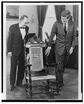 """En la Imagen el Canciller Dominicano del Consejo de Estado José Antonio Bonilla Atiles hace la Entrega en la Casa Blaca al Presidente Norteamericano John F. Kennedy,de"""" La Mecedora Dominicana """", Confeccionada para el Mandatario. Obsevese en el espaldar los escudos de ambas naciones. 4 de abril de 1962 EUA *La Mecedora Dominicana. El 4 de abril de 1962, el entonces Secretario de Estado de Relaciones Exteriores del Consejo de Estado, José Antonio Bonilla Atiles, fue recibido en la Casa Blanca por el Presidente Kennedy. Al ser recibido en uno de los salones de la mansión presidencial, le entregó de regalo al presidente una mecedora hecha en la República Dominicana y confeccionada especialmente para él. El gesto del canciller dominicano fue destacado por la prensa nacional e internacional. La agencia de prensa UPI -United Press International-, difundió una foto del encuentro, publicada en la primera plana del periódico El Caribe (5-4-62), con el siguiente texto: """"El presidente norteamericano John F. Kennedy admira el raro tallado del espaldar de una mecedora que le obsequió el canciller dominicano, licenciado J. A. Bonilla Atiles, en la Casa Blanca, en Washington. La silla es de una caoba cuatro veces centenaria del viejo edificio colonial Castillo de San Diego y al tope del respaldo tiene los escudos de Estados Unidos y la República Dominicana. El mueble es obra del ebanista Pascual Palacios."""" (UPI) Fuente de la Informacion : Articulo de René Fortunato para Diario Libre.2 dic. 2010 Fuente de la Imagen : UPI"""